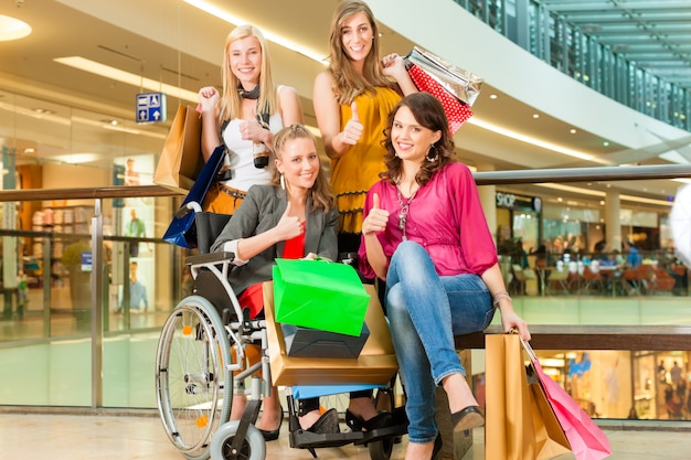 Four female friends shopping in a mall with wheelchair Premium Photo