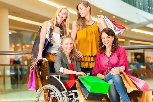 Four female friends shopping in a mall with wheelchair Premium Photo