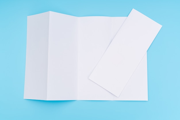 Four- fold white template paper on blue background . Free Photo