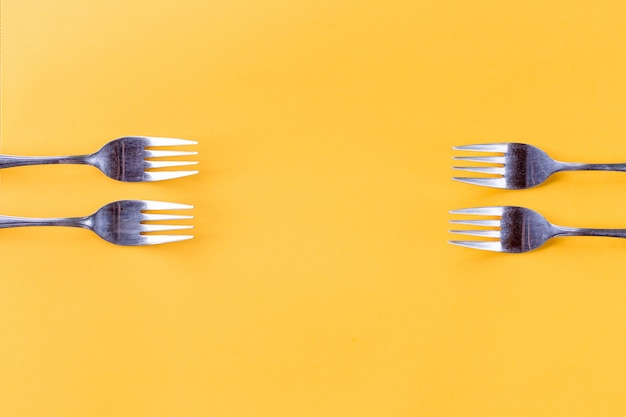 Four forks on yellow background Premium Photo