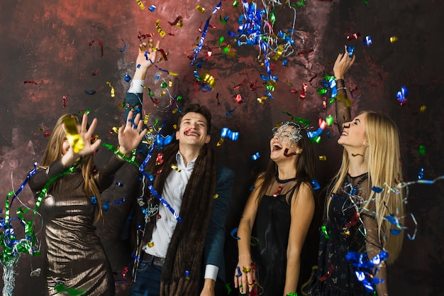 Four friends celebrating 2018 with confetti Free Photo