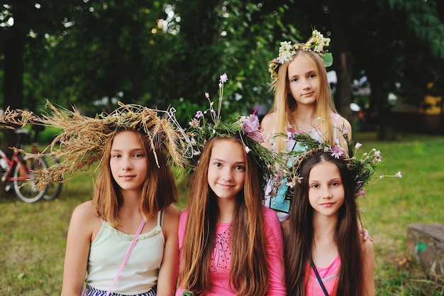 Four girls in wreaths of their wild flowers against the background of nature Premium Photo