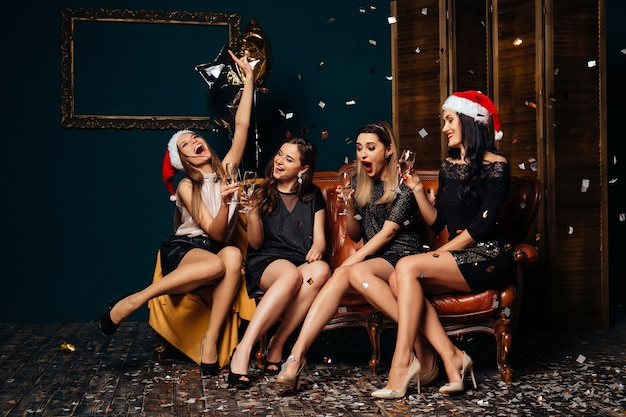 Four glamour women drinking champagne and having fun. party and christmas concept. Free Photo