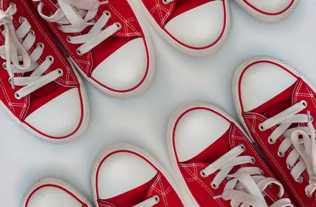 Four pairs of red sneakers on a white wooden surface Premium Photo