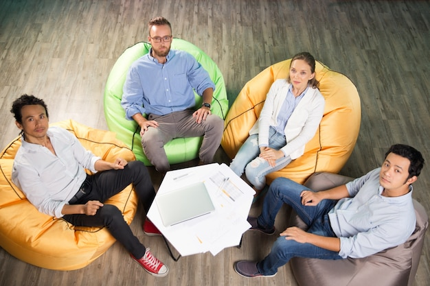 Four People Sitting On Beanbag Chairs Around Table Photo
