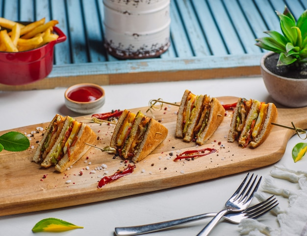 Four pieces of club sandwich on wooden board with french fries, ketchup Free Photo