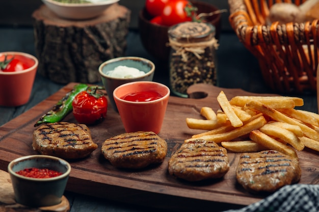 Four pieces of grilled steak patties with fries, mayo, ketchup, grilled vegetables Free Photo