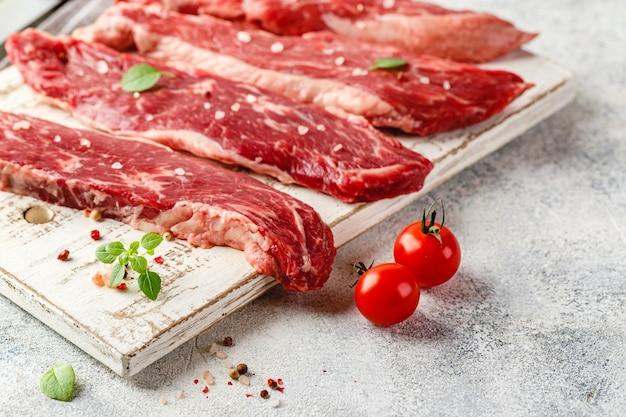 Четыре куска сырого говяжьего стейка на деревянной разделочной доске, нож, соль, перец, помидоры и масло в бутылке Premium Фотографии