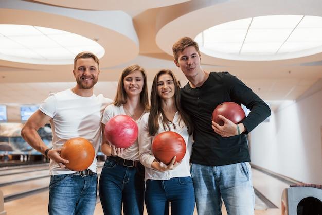 Quattro persone positive. i giovani amici allegri si divertono al bowling durante i fine settimana Foto Gratuite