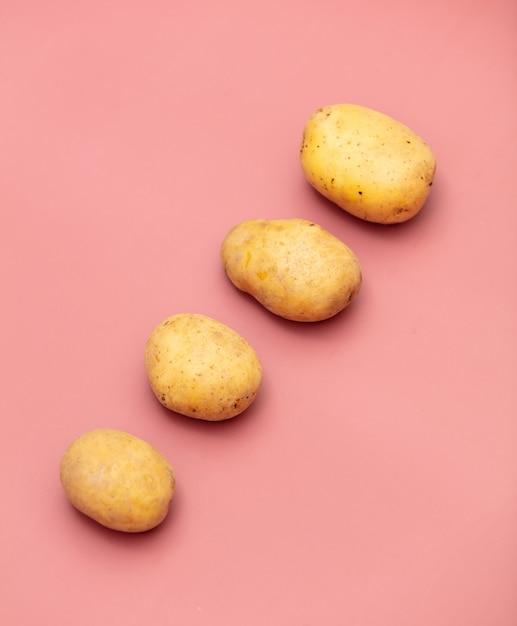 Four potatoes on pink background Premium Photo