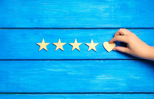 Four stars and heart on a blue background. rating five stars, the choice of the editorial Premium Photo