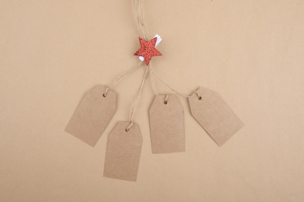 Four tags of recycled kraft paper hanging from a rope decorated with a clothespin with a red christmas star Premium Photo
