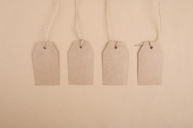 Four tags of recycled kraft paper hanging from a rope on a kraft paper. flat lay Premium Photo