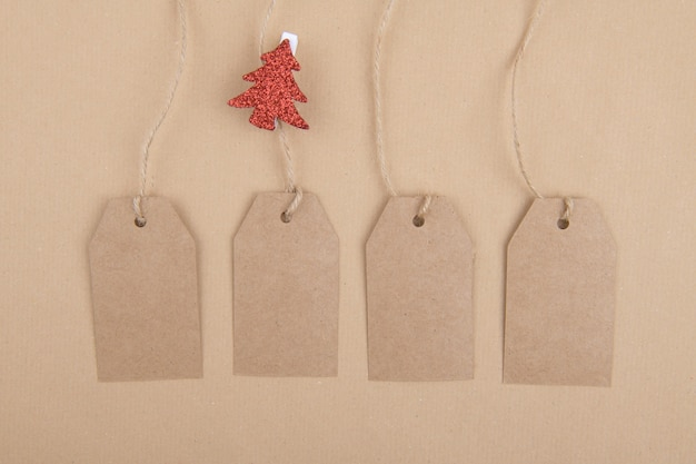 Four tags of recycled kraft paper hanging from a rope with a clothespin with a red christmas tree on kraft paper. flat lay Premium Photo