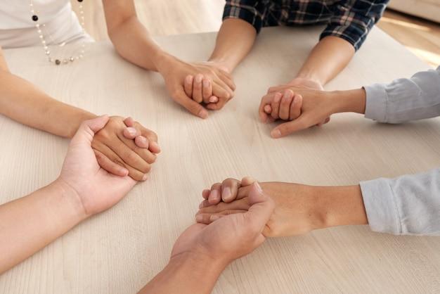 인식 할 수없는 네 명의 사람들이 테이블 주위에 앉아서 서로의 손을 잡고 무료 사진