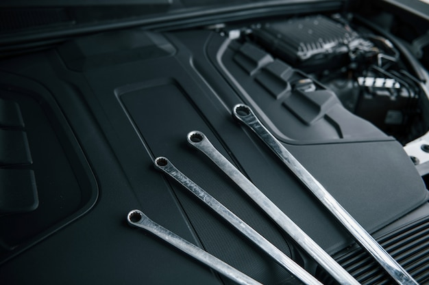 Four wrenches. repair tools leaning under the hood of automobile. silver colored Free Photo