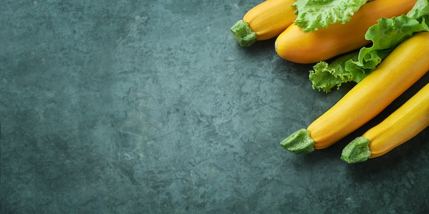 Four yellow zucchini and lettuce on kitchen table. whole raw courgettes Premium Photo