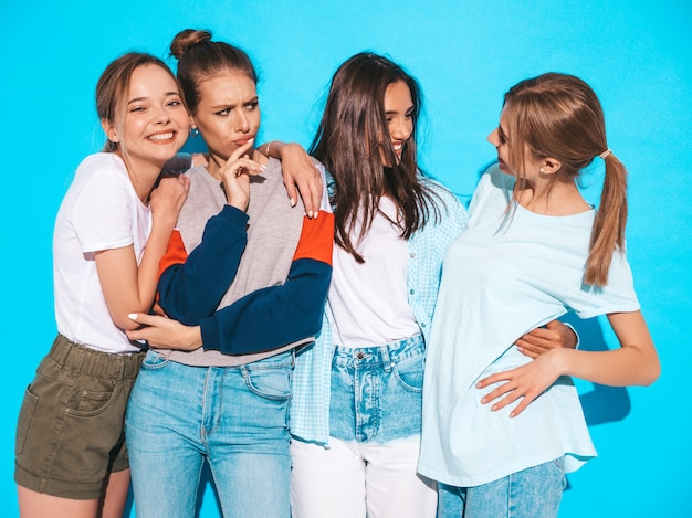 Four young beautiful smiling hipster girls in trendy summer clothes. sexy carefree women posing near blue wall in studio. positive models having fun and hugging Free Photo