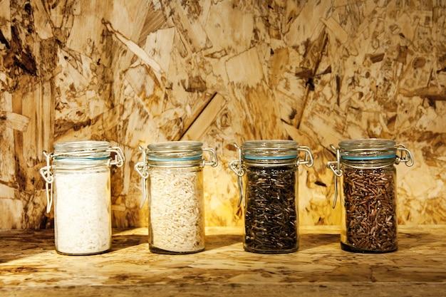 Foure раса сортов риса в стекле: коричневый рис, смешанный дикий рис, рис жасмина, рисовое зерно на деревянной полке Premium Фотографии