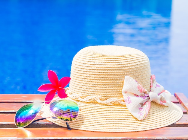 Fower with summer hat and sunglasses by the swimming pool Premium Photo