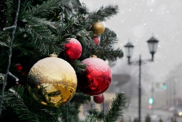 ランタンや建物のぼやけた背景に屋外で雪で軽く覆われた赤と黄色のボールで飾られたクリスマスツリーの断片。 Premium写真