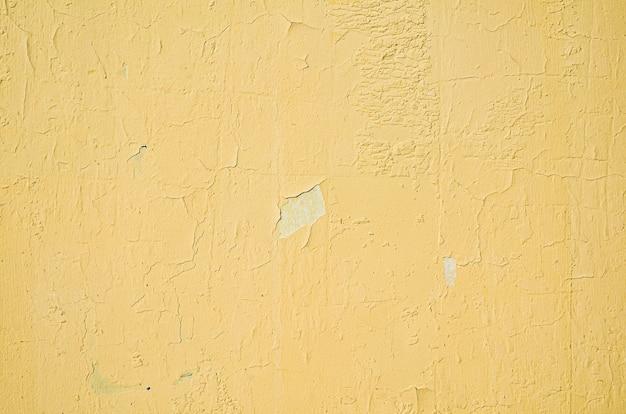Фрагмент желтой стены с царапинами и трещинами. шероховатая потрескавшаяся желтая краска для стен отслаивается. старая краска отслаивается от фона текстуры стены. Premium Фотографии