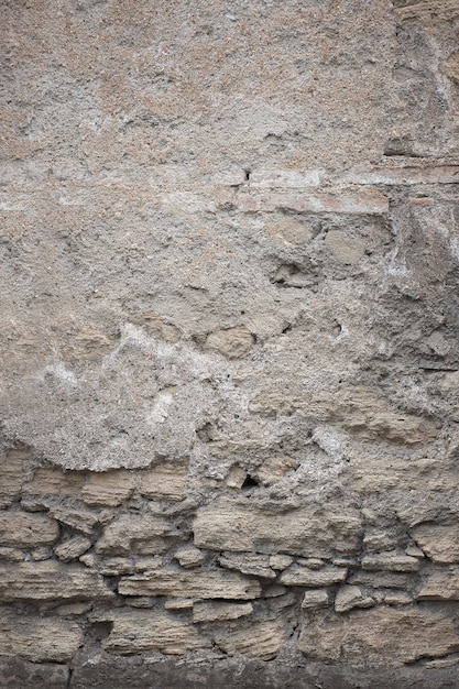 Fragment of old grungy texture with chipped paint and cracks or grey concrete wall and cement surface Free Photo
