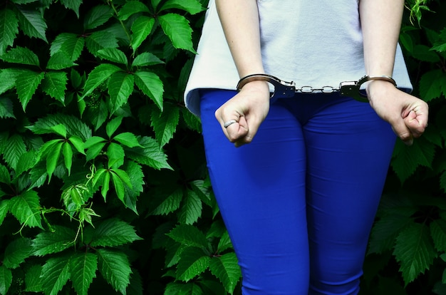 Fragment of a young criminal girl's body with hands in handcuffs Premium Photo