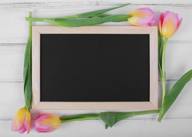 Frame blackboard around tulips Free Photo