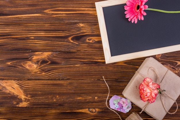 Frame blackboard decorated flowers and present box Free Photo