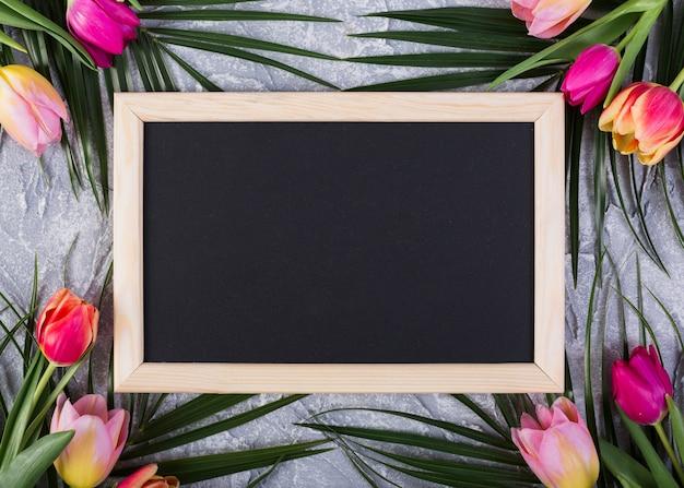 Frame blackboard with flowers along edges Free Photo