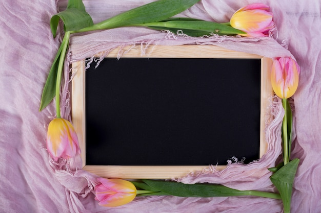 Frame blackboard with tulips on shawl Free Photo