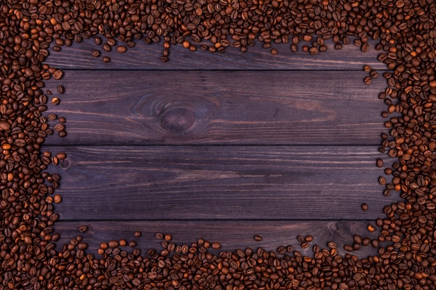 Frame of coffee beans on dark wooden background. top view with copy space Premium Photo