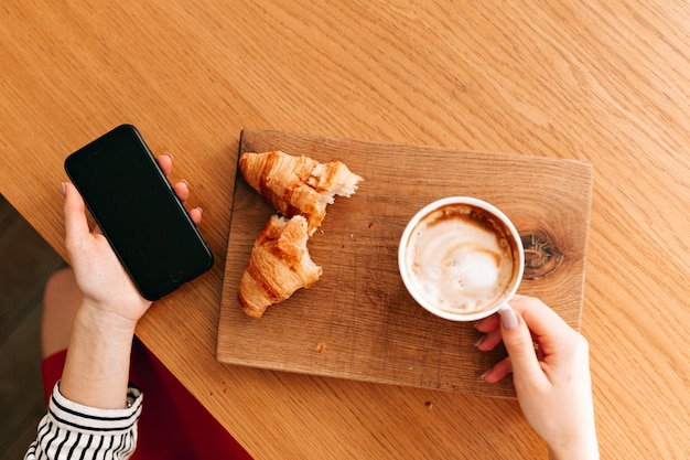Cornice sopra di una tazza di caffè con croissant su lastra di legno. Foto Gratuite