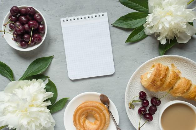 Frame custard cakes cherry flowers peony notepad tea cup. Premium Photo