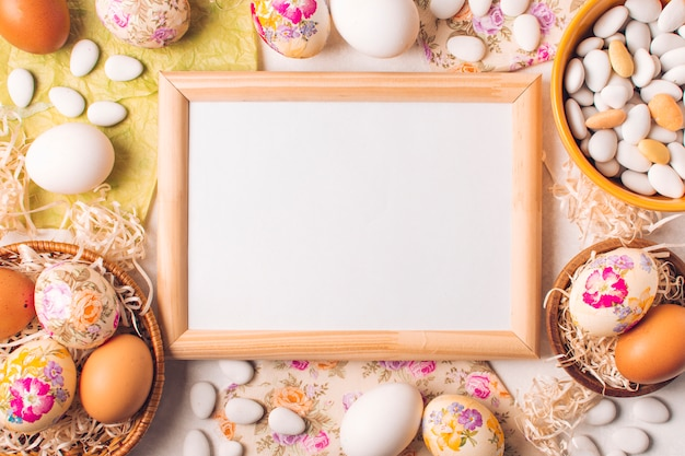 Frame between easter eggs on plates and little stones in bowl Free Photo