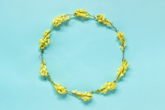 Frame floral round wreath of yellow flowers on blue background. Premium Photo