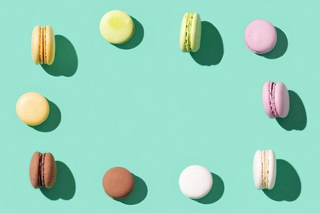 鮮やかな青緑色の各種マカロンのフレーム、カラフルなフレンチクッキーマカロン Premium写真
