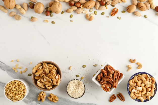 Frame made of different types of nuts in bowls. top view. copy space Premium Photo