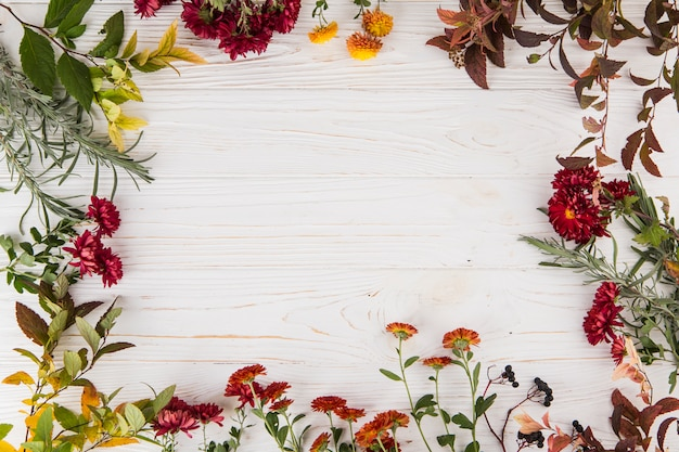 Frame made from different flowers on table Free Photo