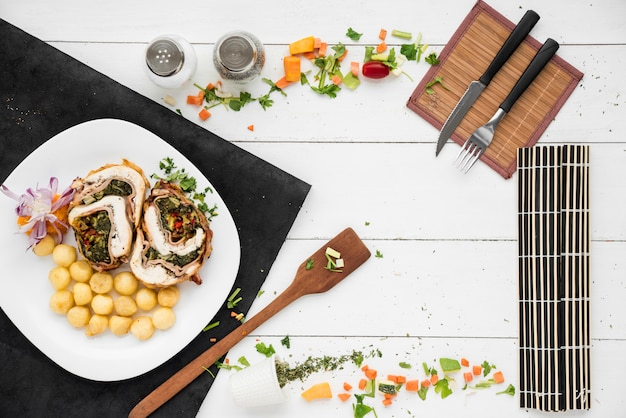 Frame made of meat roll and gnocchi dish, tableware and vegetable pieces Free Photo