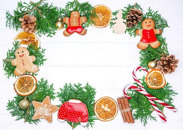 Рама из рождественского печенья и елки на белом фоне. Premium Фотографии