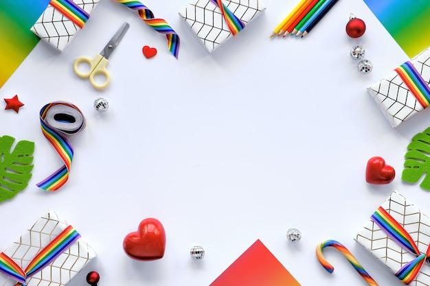 Lgbtqコミュニティの旗の色のレインボーリボンとクリスマスプレゼントで作られたフレーム。 Premium写真