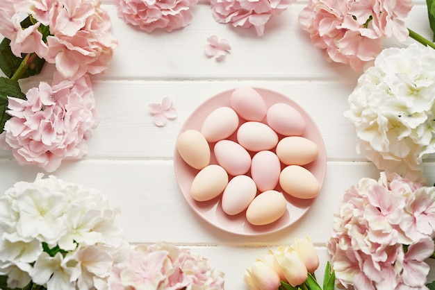 Frame made of pink and beige hydrangea flowers, pink eggs and yellow tulips Premium Photo