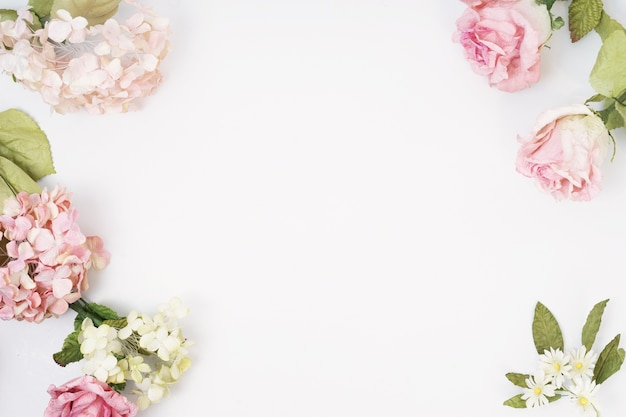 Frame made of pink and beige roses, green leaves on white background. Premium Photo