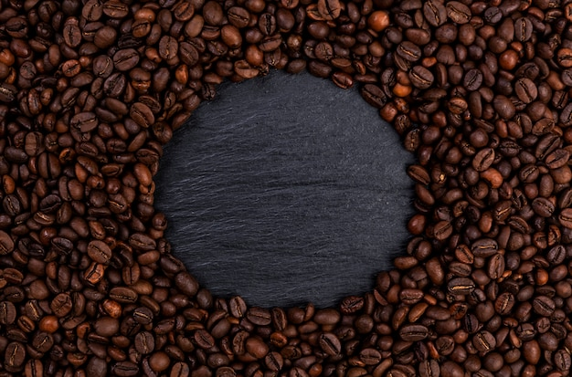 Frame made of roasted coffee beans on black table, top view Premium Photo