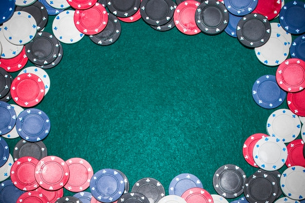 Frame made with casino chips on green poker table Free Photo
