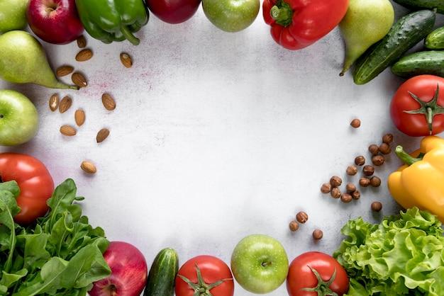 カラフルな果物で作られたフレーム。野菜とドライフルーツの白い表面 無料写真