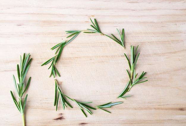 Каркас из свежего органического розмарина на деревянном столе Premium Фотографии