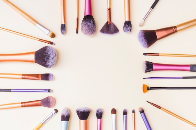 Frame made with set of makeup brushes on beige background Free Photo